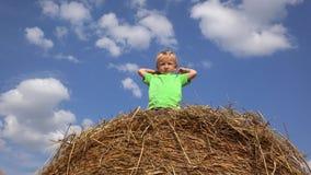 Het grappige kind schikt stro op zijn hoofd, vermakelijke ogenblikken, de mooie rustieke zomer stock footage