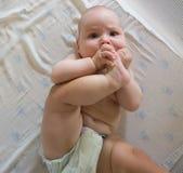 Het grappige kind spelen met zijn voet Royalty-vrije Stock Afbeelding