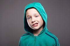 het grappige kind van de grimasemotie jongen in Kap stock afbeeldingen