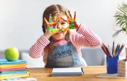 Het grappige kindmeisje trekt het lachen toont handen vuil met verf Stock Fotografie