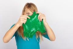 Het grappige meisje die groen slijm houden kijkt als gunk voor haar gezicht royalty-vrije stock foto