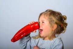 Het grappige meisje heeft pret met paprika stock afbeeldingen