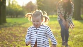 Het grappige Meisje loopt vanaf Haar Mamma De moeder en de Dochter in Gestreepte Kleren spelen samen van het Genieten stock video