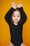 Het grappige meisje maakt konijntjesoren door handen op oranje achtergrond Exemplaar-ruimte Royalty-vrije Stock Foto's