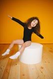 Het grappige meisje maakt vliegtuigvleugels door handen op oranje achtergrond Exemplaar-ruimte Stock Foto's