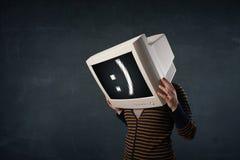 Het grappige meisje met een monitordoos op haar hoofd en een smiley zien onder ogen stock foto's