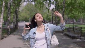 Het grappige meisje met lang haar loopt onderaan de straat en danst luisterend aan muziek op hoofdtelefoons stock footage