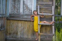 Het grappige meisje spelen dichtbij dorpshuizen stock fotografie