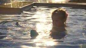 Het grappige meisje spelen in zwembad stock videobeelden