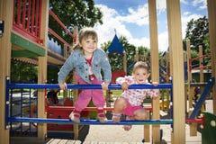 Het grappige meisje twee spelen op de speelplaats Royalty-vrije Stock Foto's