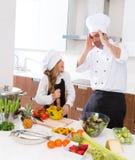 Het grappige meisje van het chef-kok hoofd en ondergeschikte jonge geitje bij het koken van gekke school Royalty-vrije Stock Afbeeldingen