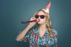 Het grappige meisje viert haar verjaardag Zij houdt fluitje in haar mond en houdt het met een hand Ook heeft zij haar stock afbeelding