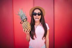 Het grappige meisje in zonnebril bevindt zich en toont haar tong De vrouw houdt ananas met glazen Zij stelt op camera royalty-vrije stock foto's