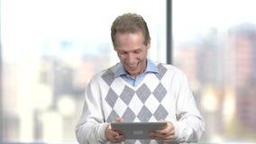 Het grappige mens spelen op middelbare leeftijd op digitale tablet stock video