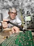 Het grappige nerdwetenschapper solderen bij laboratorium stock fotografie