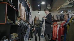 Het grappige paar doen die in weekend en meisje winkelen geeft haar vriendpartijen van kleren aan greep voor haar op zwarte vrijd stock video