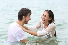 Het grappige paar het gekscheren baden op het strand royalty-vrije stock afbeeldingen