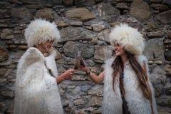 Het grappige paar in nationale wollen kleren drinkt van traditionele glazen stock afbeelding