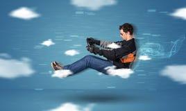 Het grappige racedriver jonge mens drijven tussen wolkenconcept Royalty-vrije Stock Foto's