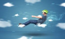 Het grappige racedriver jonge mens drijven tussen wolkenconcept royalty-vrije stock foto