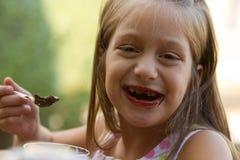 Het grappige tandenloze meisje eet roomijs Stock Foto