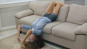 Het grappige tienermeisje ontspannen op bankbovenkant - onderaan het gebruiken van laptop en het surfen van Internet stock footage