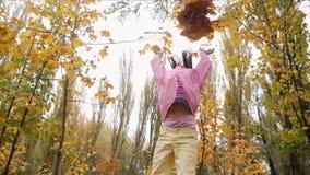 Het grappige, vrolijke leuke meisjesprong werpen op de gele herfst gevallen verlaat langzame motie stock videobeelden