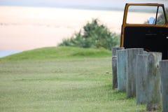 Het gras naast parkeerterrein leidt tot strand Stock Foto