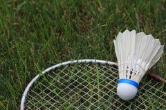 Het Gras van badmintonbirdie shuttlecock racket on green Stock Afbeeldingen