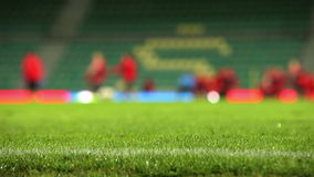 Het gras van het voetbalgebied met regendalingen met unfocused team opleidingsproces op de achtergrond stock video