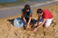 Het graven onder het zand Stock Foto