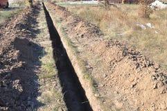Het graven van een geul Grondwerken, gravende geul Lange aarden die geul wordt gegraven om pijp of optische vezel te leggen stock foto