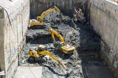 Het graven van graafwerktuigenbaggers bij een bouwwerf Stock Foto's