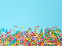 Het grenskader van kleurrijk bestrooit op blauwe achtergrond royalty-vrije stock foto