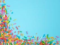 Het grenskader van kleurrijk bestrooit op blauwe achtergrond royalty-vrije stock afbeelding