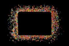 Het grenskader van kleurrijk bestrooit op een zwarte achtergrond met mede stock foto's