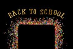 Het grenskader van kleurrijk bestrooit op een zwarte achtergrond met mede stock foto