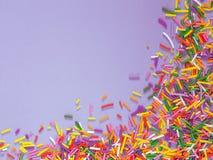 Het grenskader van kleurrijk bestrooit op lilac purpere achtergrond stock afbeelding