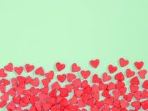 Het grenskader van rode haard-vorm bestrooit op groene achtergrond royalty-vrije stock afbeeldingen
