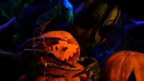 Het griezelige donkere schepsel knuffelt een gesneden pompoen stock video