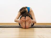 Het grijpen van haar voeten om de benen uit te rekken Stock Foto's