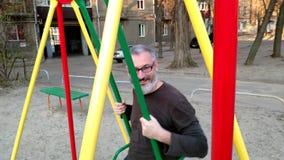 Het grijs-haired gebaarde personenvervoer op een schommeling, verheugt zich en glimlacht, concept gelukkige kinderjaren stock videobeelden