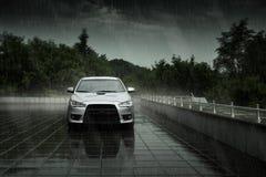 Het grijze autoverblijf en denkt in natte weg in zware regen na bij dag royalty-vrije stock afbeeldingen