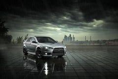 Het grijze autoverblijf en denkt in natte weg in zware regen na bij dag stock foto