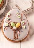 Het grijze koekje van Pasen met decoratieve paaseieren en bloemen dichtbij witte scherpe raad stock afbeeldingen