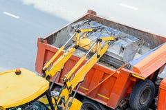 Het grint van de tractorlading in een vrachtwagen De werken van de weg stock afbeelding