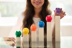 Het Groeien van onderneemsterplacing piggybank on Grafiek stock afbeeldingen