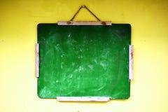 Het groene balackboard hangen op een gele muur stock fotografie