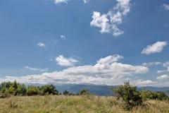 Het groene gras van de zomerbergen en blauwe hemel met wolken Royalty-vrije Stock Afbeeldingen