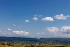 Het groene gras van de zomerbergen en blauwe hemel met wolken Royalty-vrije Stock Fotografie